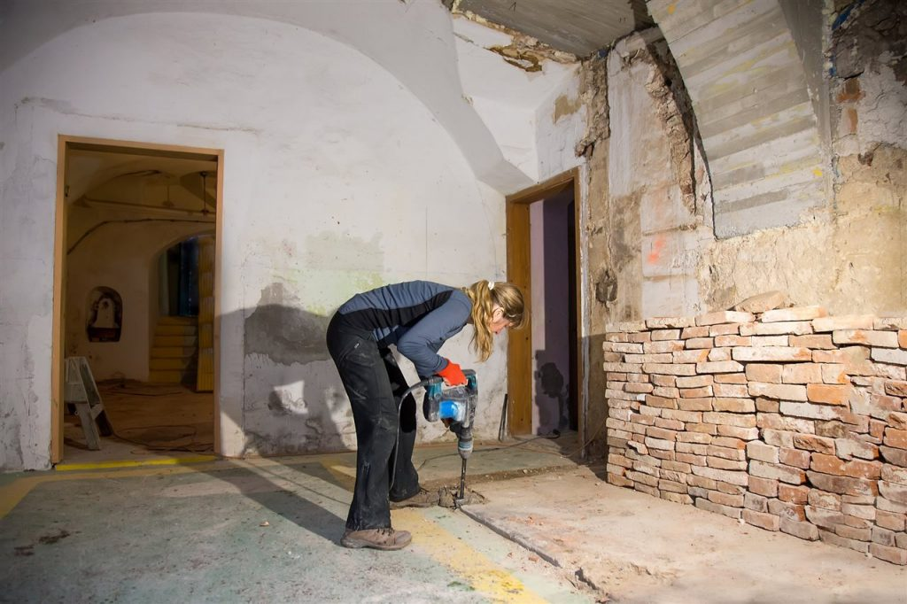 woman drilling the basement floor | Lighthouse Inspections | Bathroom in the basement Connecticut