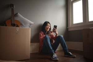 a girl sitting looking at her phone smiling | Lighthouse Inspections | moving made easy dallas Connecticut